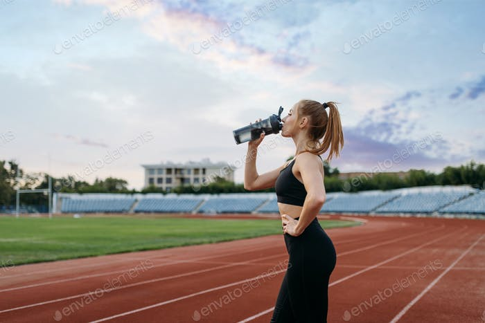Female runner drinks water, training on stadium
