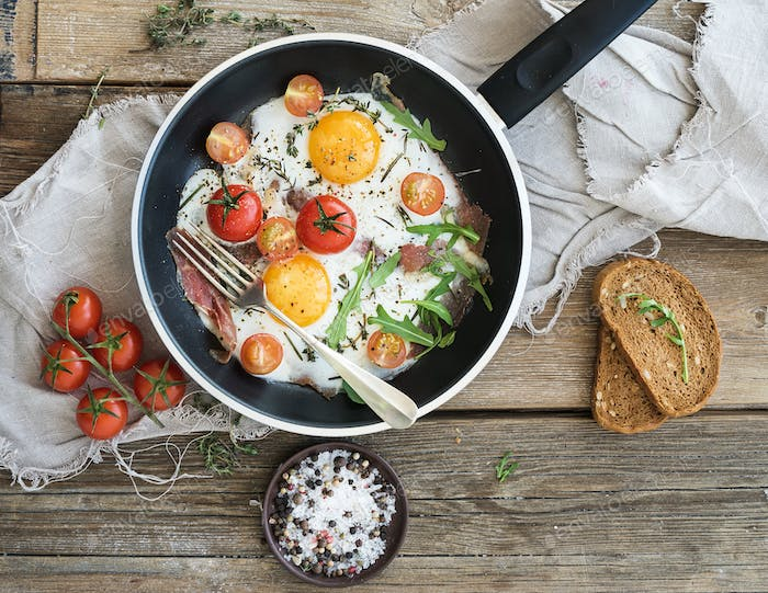 Pan of fried eggs, bacon and cherry-tomatoes with bread