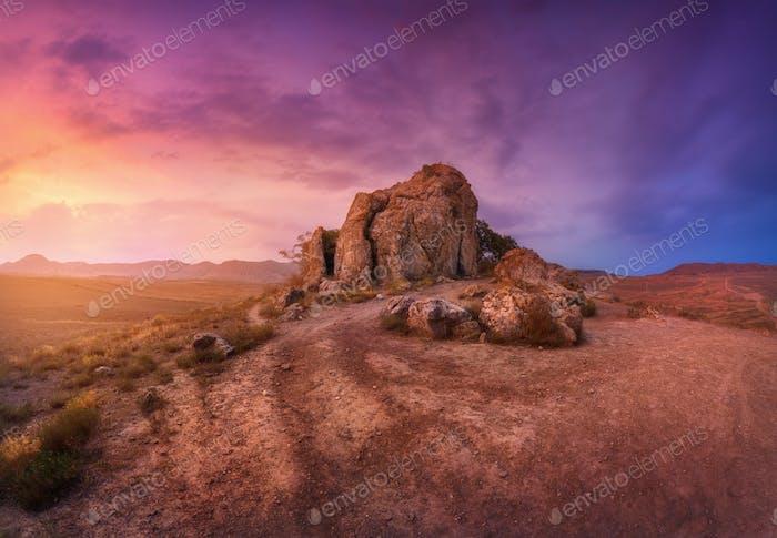 Wüste mit einsamen Felsen gegen mehrfarbigen bewölkten Himmel