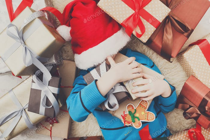 Happy child with Christmas present boxes and gifts, top view