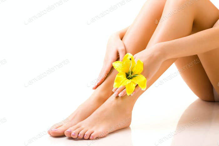 Beautiful well-groomed legs of girl with a flower
