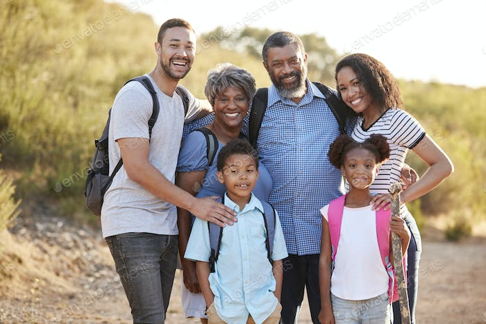 Portrait Of Multi Generation Family Wearing Backpacks Hiking In Countryside Together