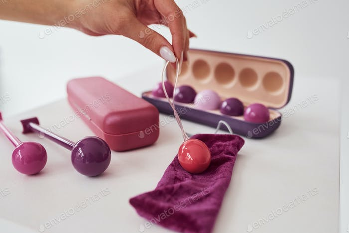 Close up view of pink vaginal balls and stimulators lying down on the table