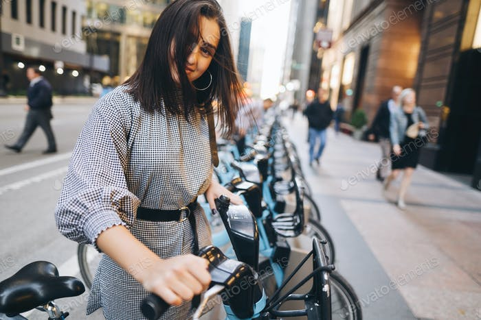 girl renting a city bike from a bike stand