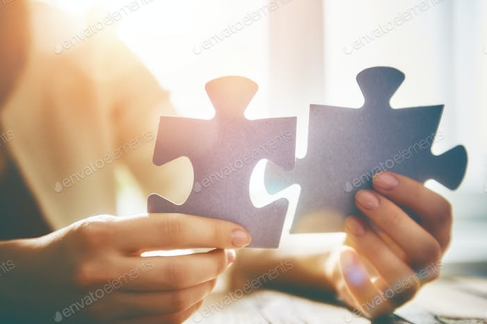 Woman connects couple puzzle piece