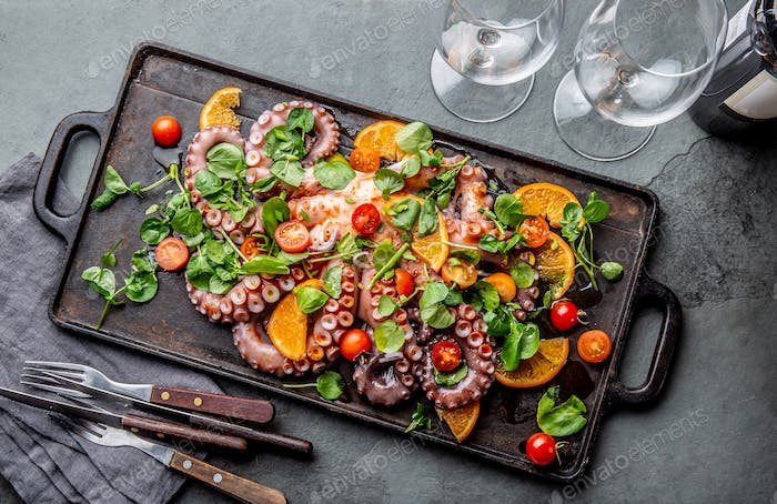 Whole octopus salad with orange, tomatoes and cress salad served on board with wine