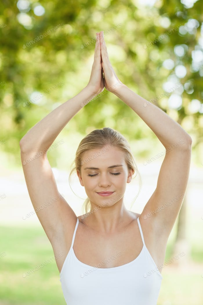 Front view of peaceful young woman doing yoga in a park with hands raised in prayer