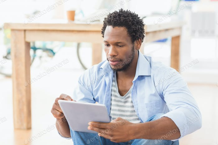 Attentive young creative businessman scrolling on the tablet