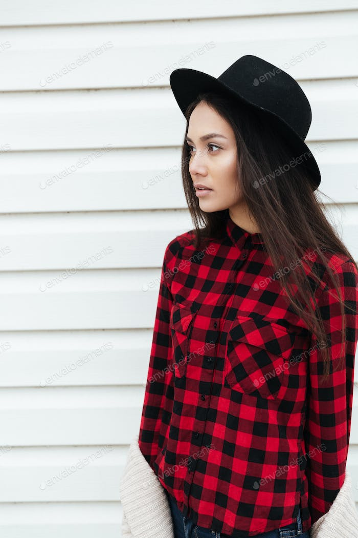 Pensive woman in checkered shirt looking away