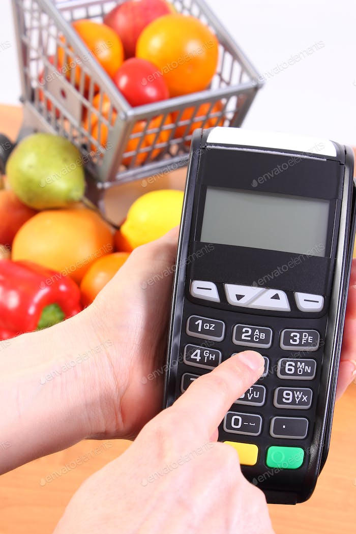 Using payment terminal, fruits and vegetables, cashless paying for shopping concept