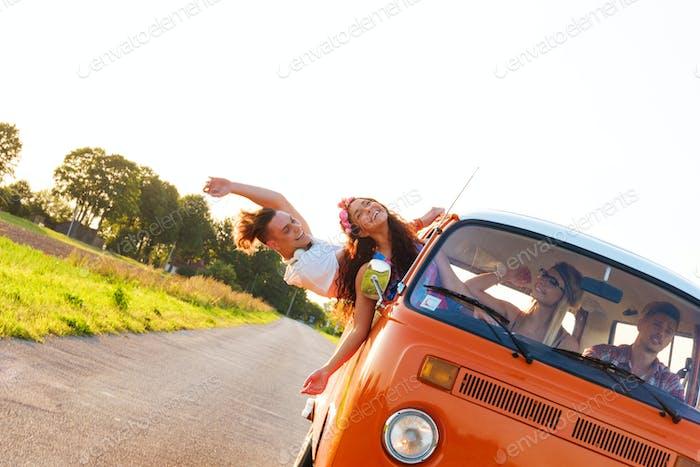 Amigos hippie en una furgoneta en un viaje por Carretera