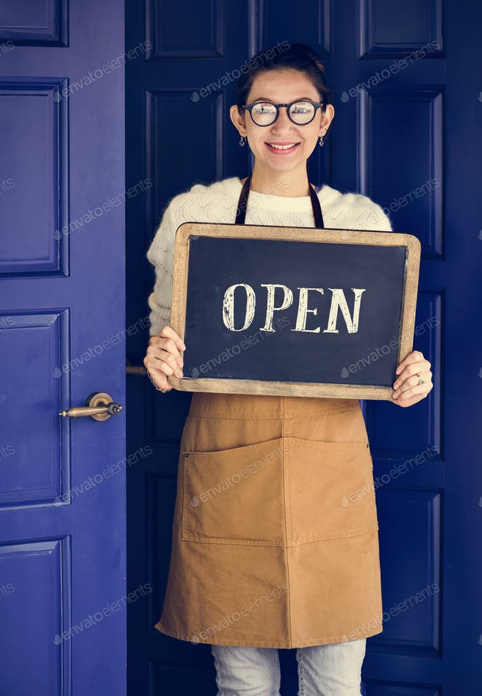A cheerful small business owner with open sign