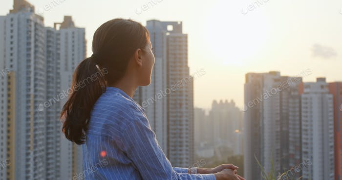 Woman look at the city view under sunset