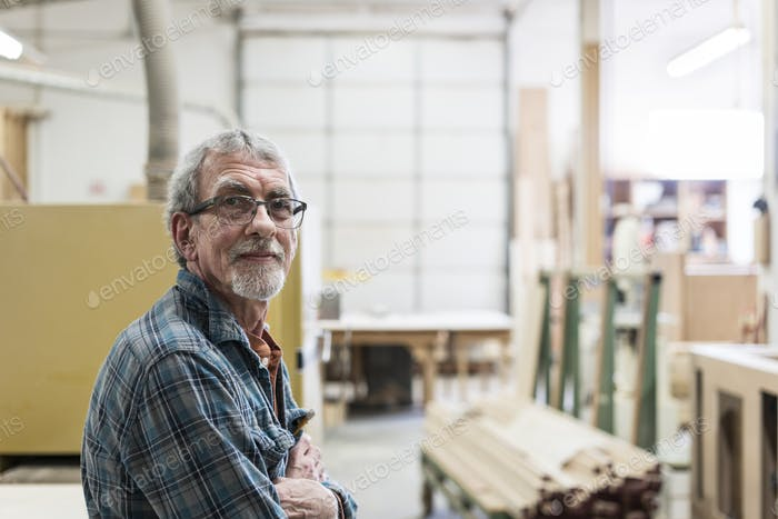 Portrait of a senior Caucasian carpenter in a large woodworking shop.