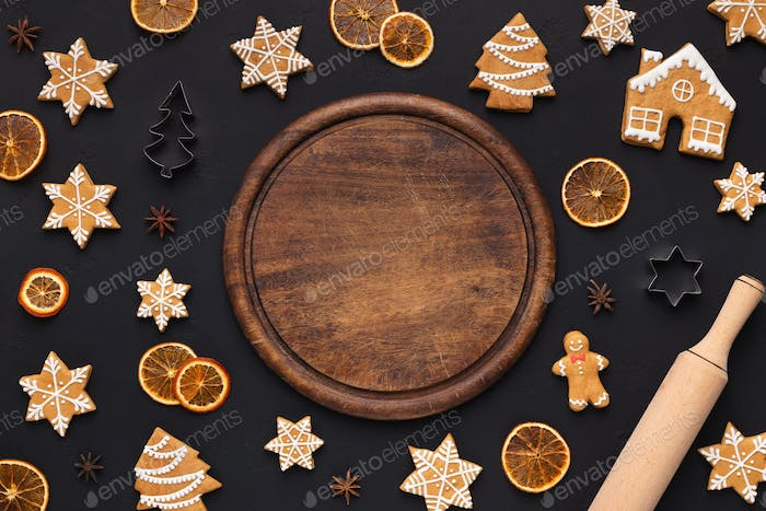 Gingerbread cookies and round wooden board, top view