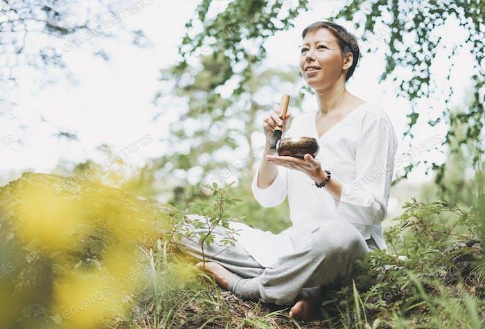 Junge lächelnde Frau spielt auf der Messing tibetischen Klangschale im Wald