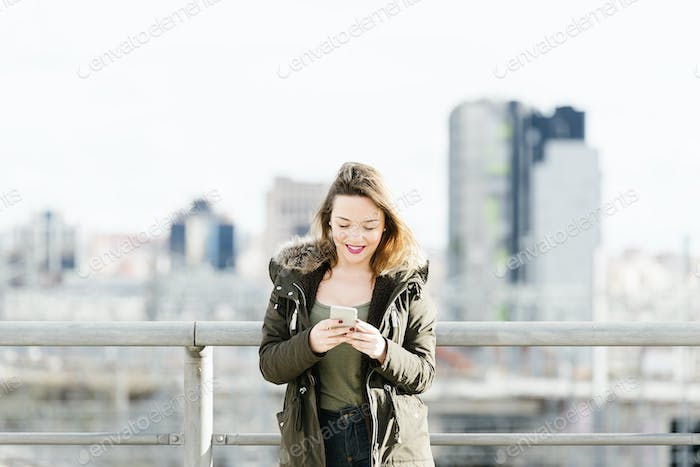 Happy girl texting on a smartphone.