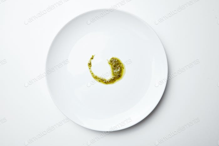 Pesto Sauce Spilled on white blank plate isolated top view