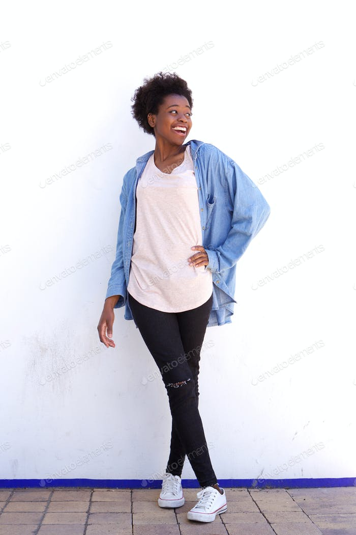 Full length young african american model posing against wall outside