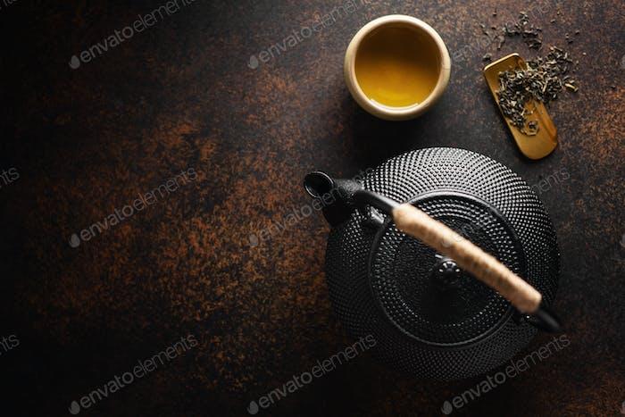 Teekanne mit Tee auf dunklem Hintergrund