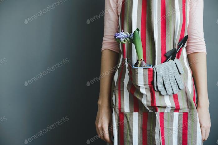 Frau steht mit Hyazinthe Pflanze und kleiner Schaufel