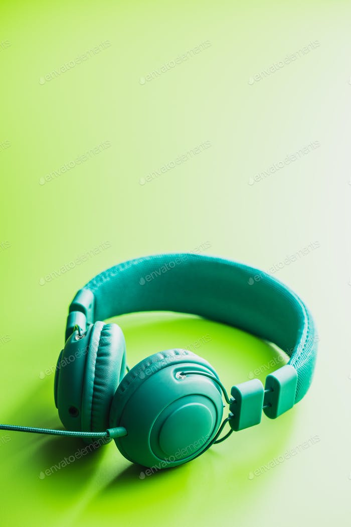 Green wired stereo headphones on green background.