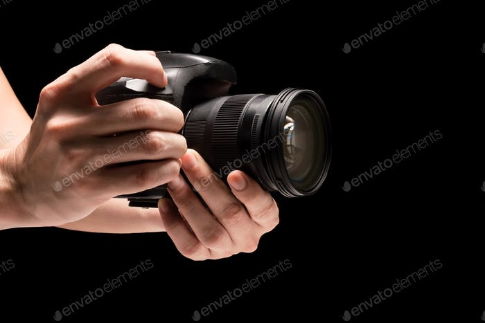 Male hand holding a digital camera on a black background.