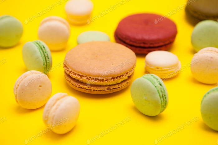 Different patterns of colorful french macaroons on yellow background