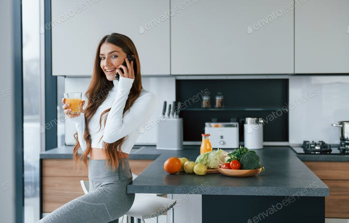 Young european woman is indoors at kitchen indoors with healthy food