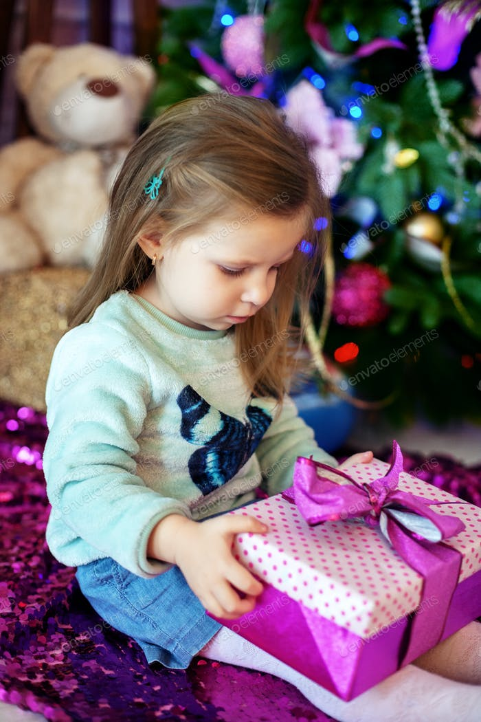 beautiful baby opens a gift. The concept of Christmas and a happ