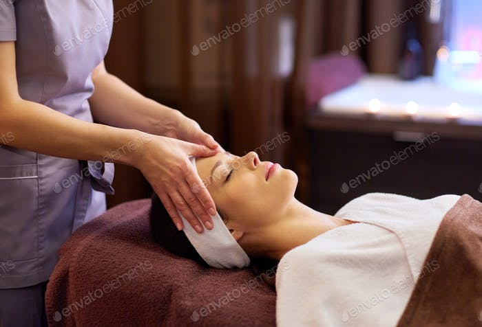 woman having face and head massage at spa
