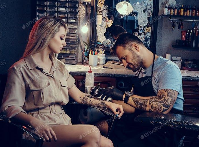 Process of tattoo making at dark photo studio