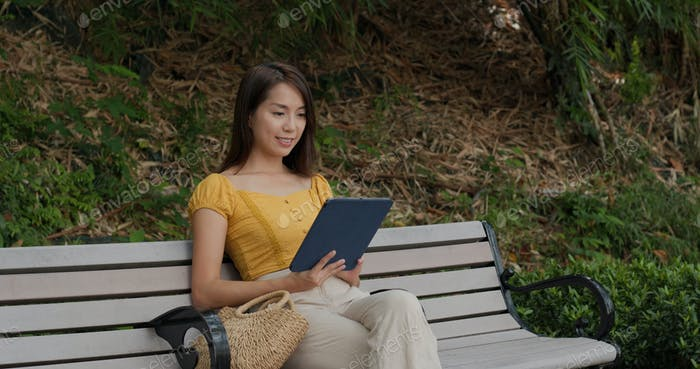 Woman use of tablet computer at park