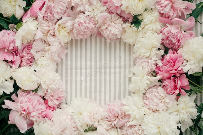 Beautiful peonies frame flat lay on rustic table cloth
