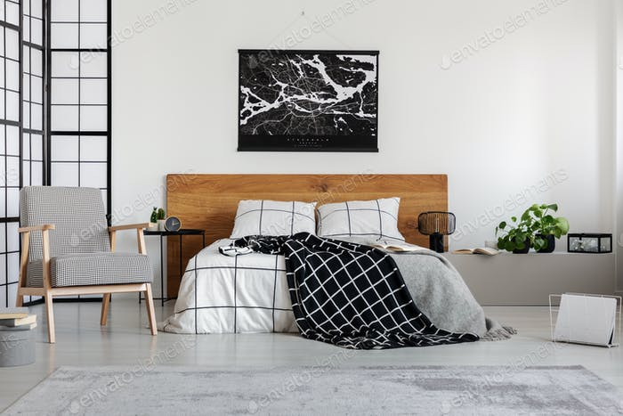 Black map on white wall above wooden headboard in simple bedroom interior