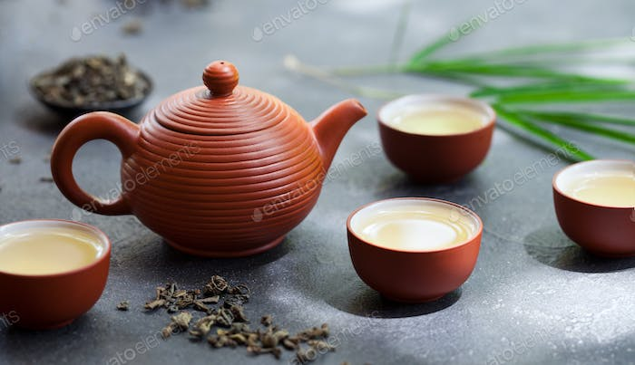 Green Tea in Tea Pot and Bowls, Cups on Slate Background. Close up.