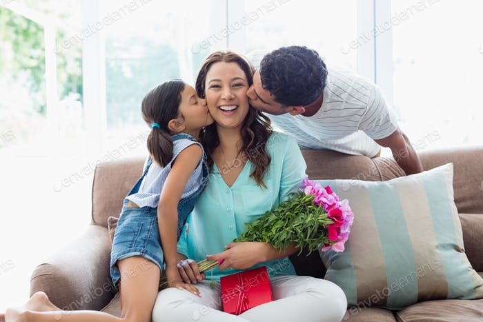 Woman receiving kiss from his husband and daughter in living room
