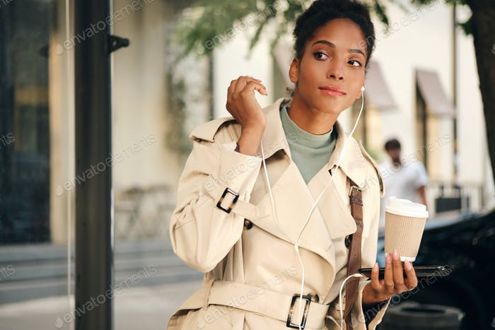 African American girl in stylish trench coat with cellphone thoughtfully waiting bus at bus stop