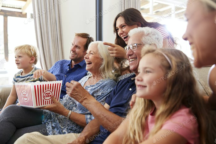 Multi-Generation Family Sitting On Sofa At Home Eating Popcorn And Watching Movie Together