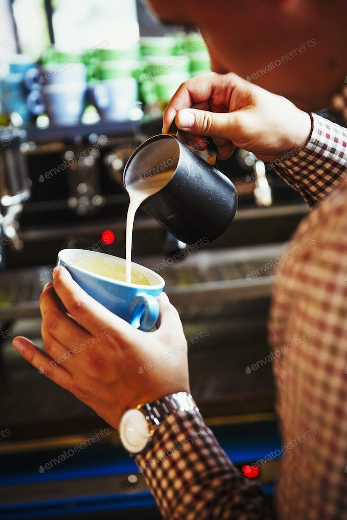 Specialist coffee shop. A person making coffee and pouring milk into a cup held at an angle.