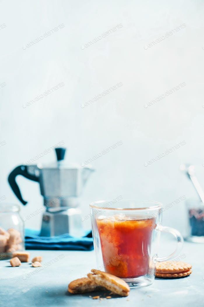 Breakfast with coffee and cookies. Double wall glass cup with a Moka pot on a light concrete