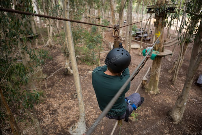 Man wearing safety helmet crossing zip line in the forest