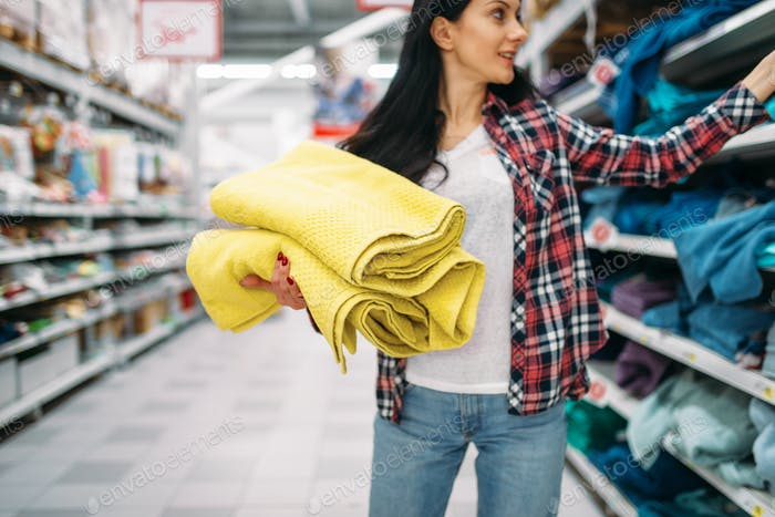 Young woman buying towels in supermarket