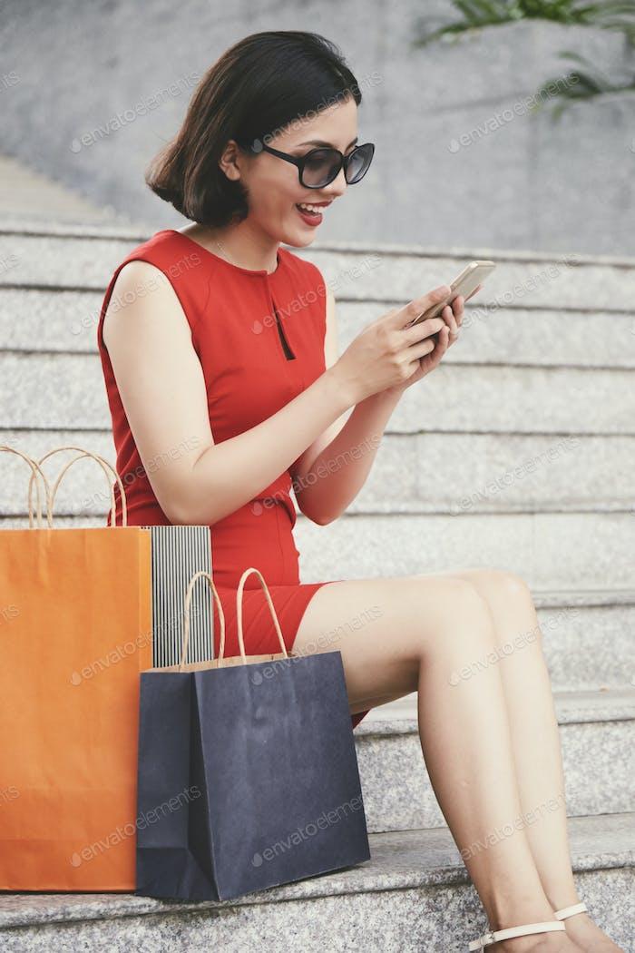 Happy shopaholic texting friends