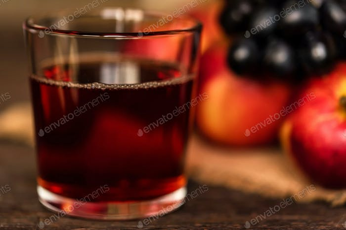 Red grape juice in glass, grapes and red apples