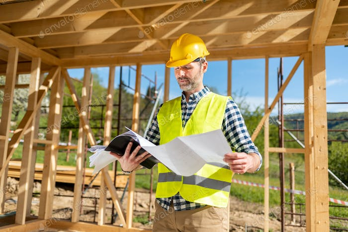 Construction engineer or architect with blueprints visiting building site of wood frame house