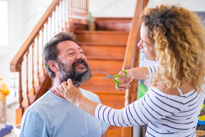 eine Frau zu Hause schneidet den Bart eines Mannes drinnen - zwei Leute haben zusammen Spaß zu Hause
