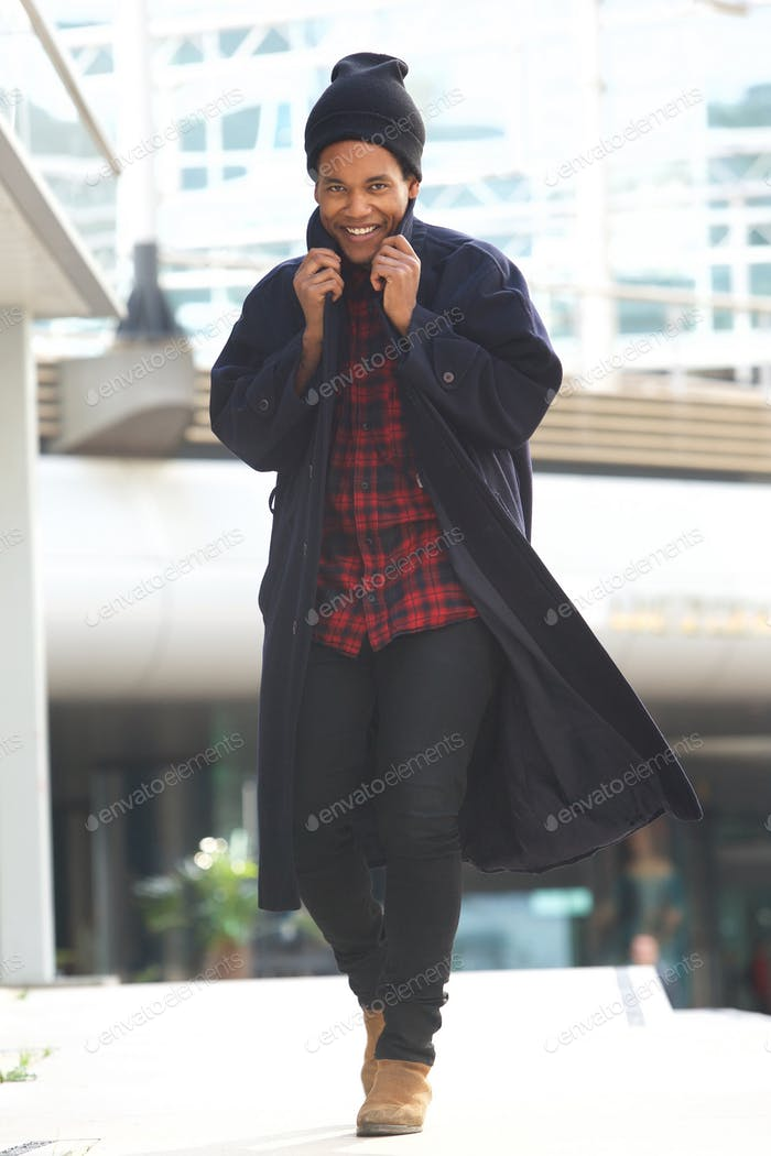 Full body trendy african american walking with winter jacket and beanie in the city