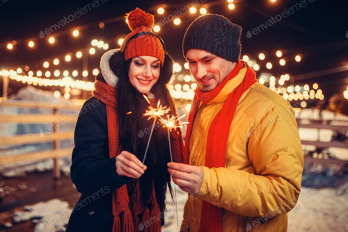 Winter evening, love couple with sparklers kissing