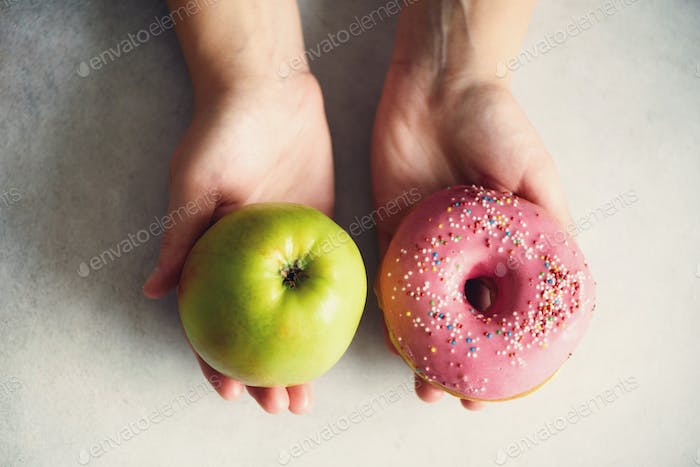 Young woman in white T-shirt choosing between green apple or junk food, donut. Healthy clean detox